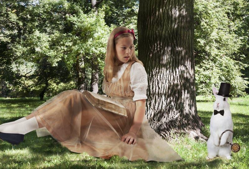 Liten flicka med en stor vit kanin arkivfoto