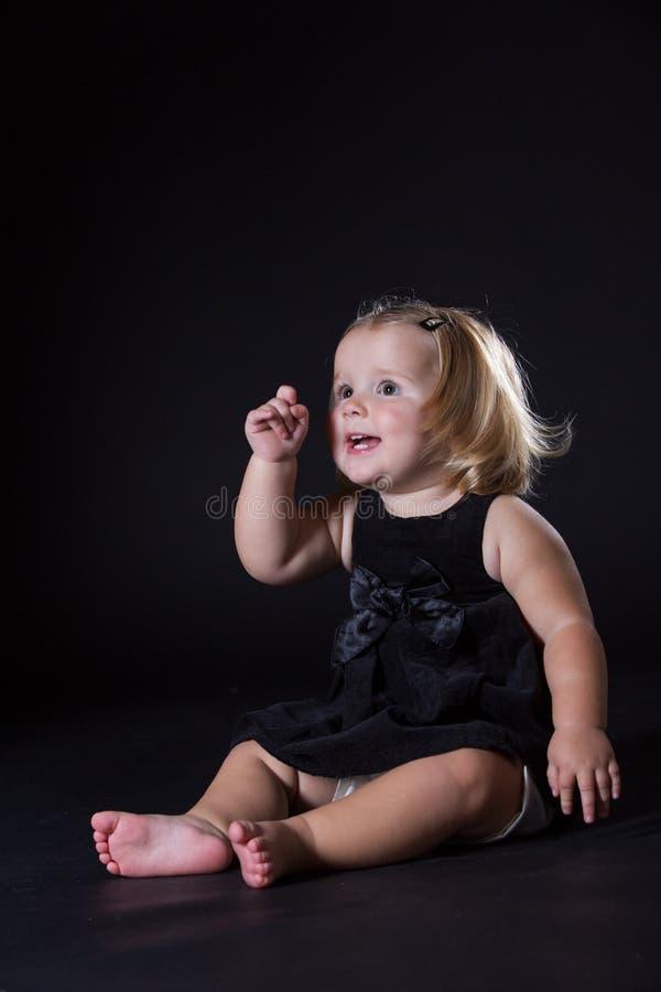 Liten flicka med en svart bakgrund royaltyfri foto