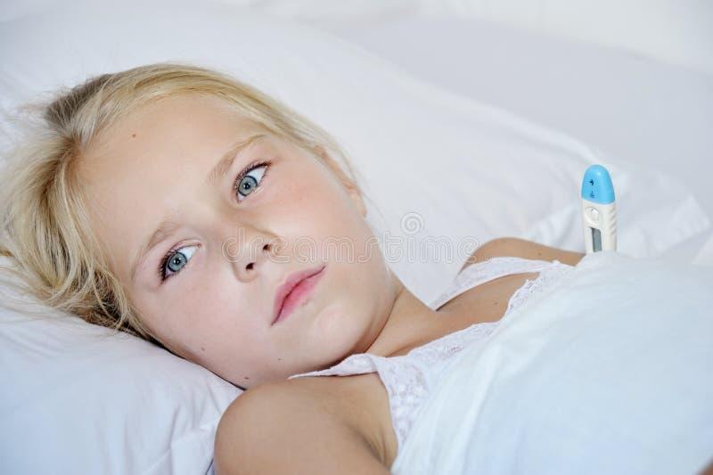 Liten flicka med en termometer som är sjuk i säng royaltyfria bilder