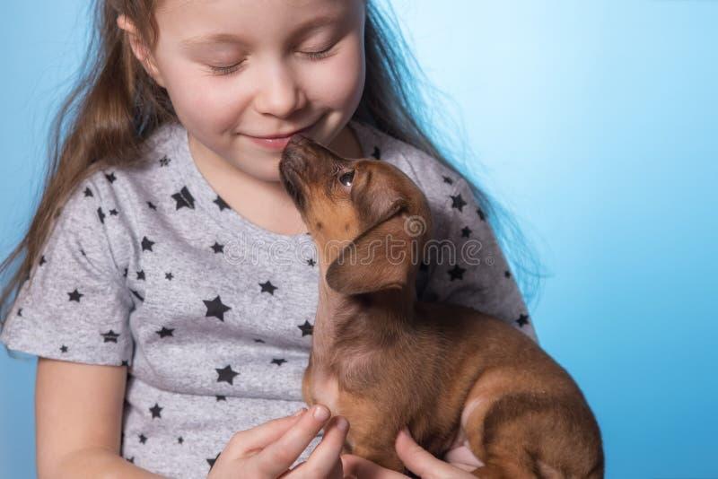 Liten flicka med en valphund i hennes armar Närbild arkivbilder
