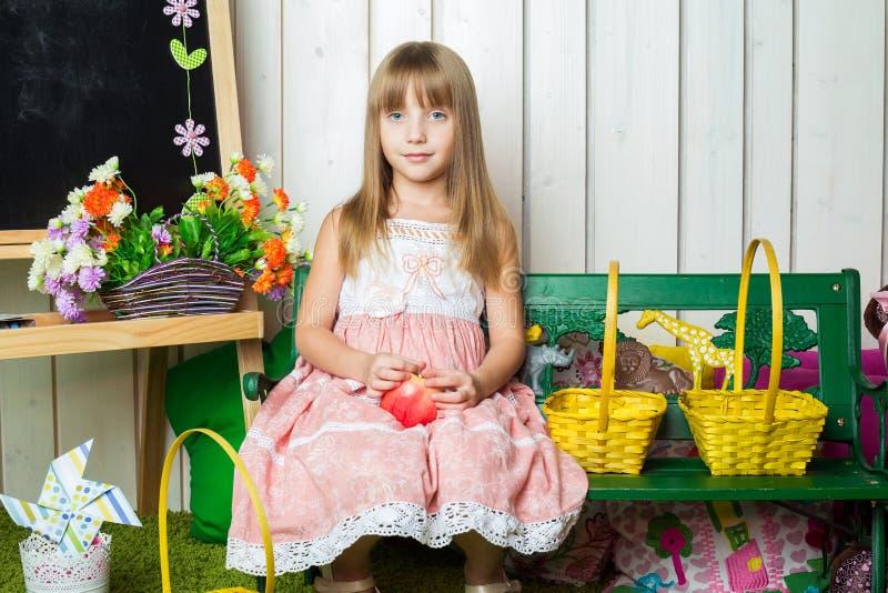 Liten flicka med ett äpple i henne sitta för händer arkivfoton