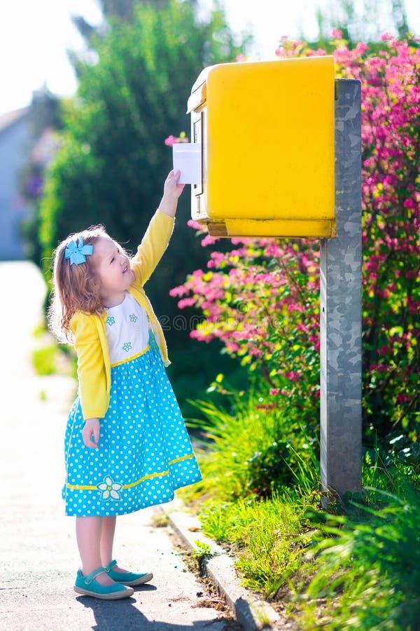 Liten flicka med ett kuvert bredvid en brevlåda arkivbild