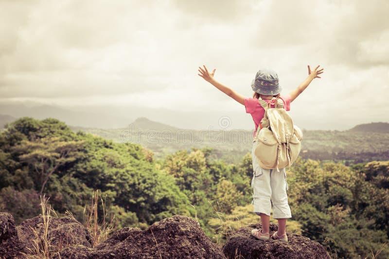 Liten flicka med ett ryggsäckanseende på en bergöverkant royaltyfri bild