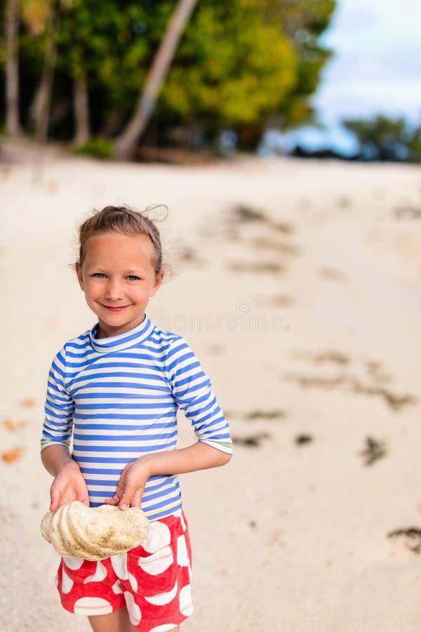 Liten flicka med ett snäckskal fotografering för bildbyråer