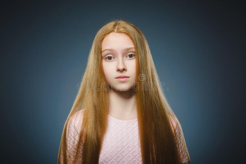 Liten flicka med förvånat uttryck, medan stå mot grå bakgrund royaltyfri fotografi