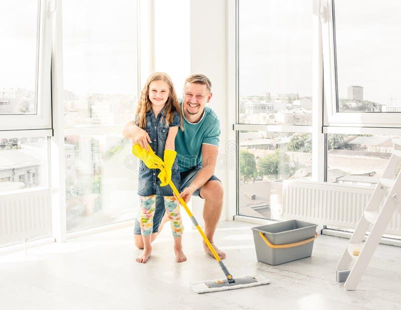 Liten flicka med fadern som gör ren golvet royaltyfri foto