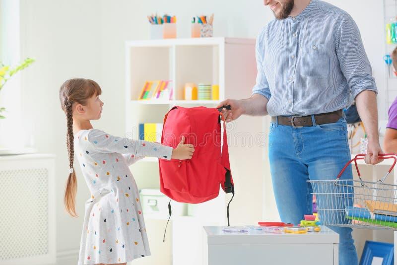 Liten flicka med fadern som väljer skolabrevpapper fotografering för bildbyråer