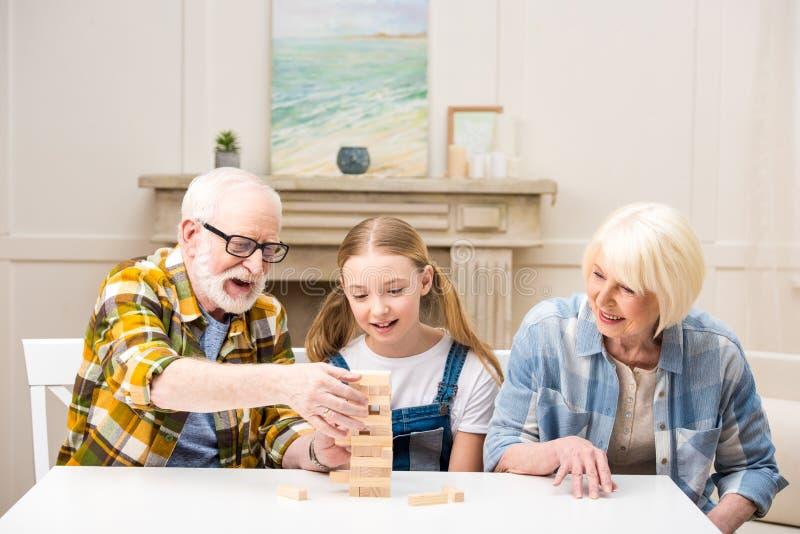 Liten flicka med farfadern och farmodern som spelar modigt hemmastatt för jenga fotografering för bildbyråer