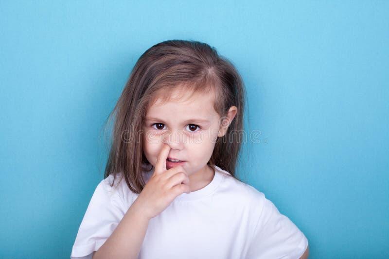 Liten flicka med fingret i hennes n?sa royaltyfri foto