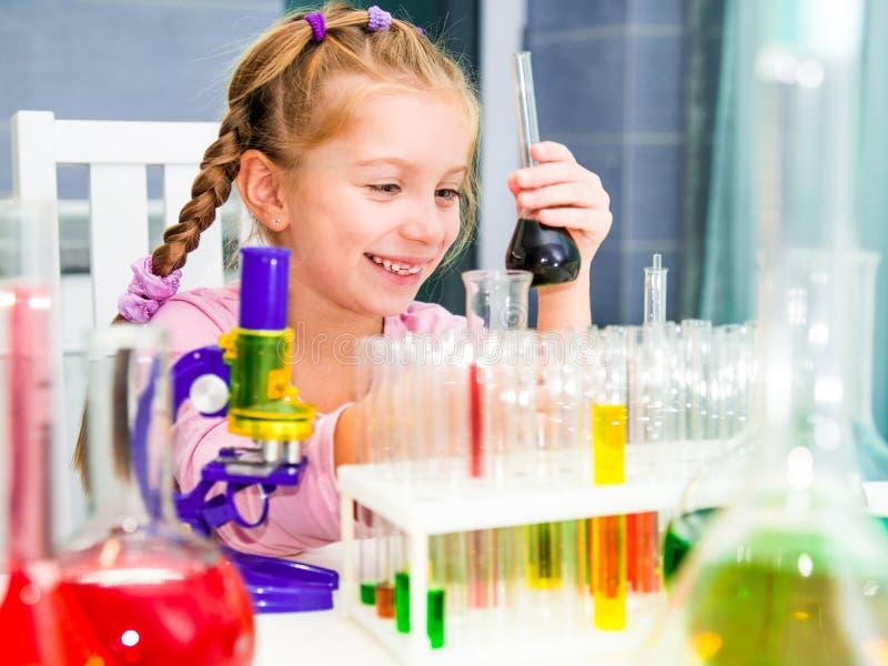 Liten flicka med flaskor för kemi royaltyfri bild