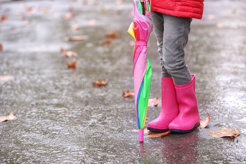 Liten flicka med gummistöveler och paraplyet efter regn, fokus av ben arkivbilder