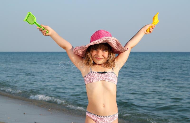 Liten flicka med händer upp på stranden royaltyfri bild