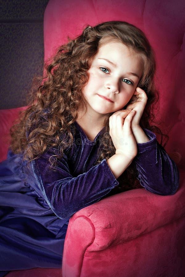 Liten flicka med härligt hår som poserar i stol royaltyfria bilder