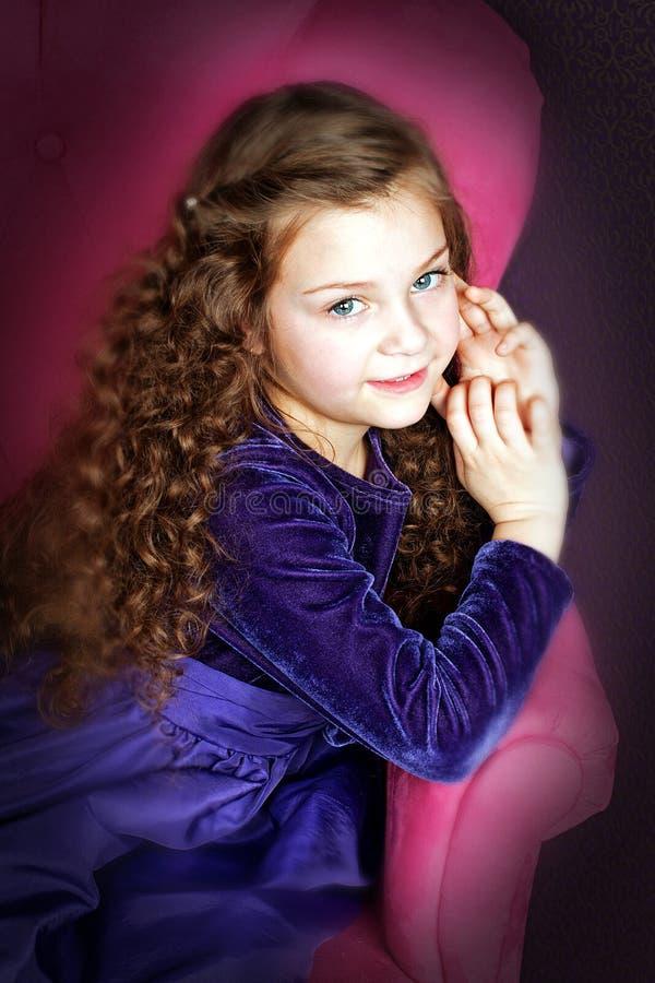 Liten flicka med härligt hår som poserar i stol arkivbild