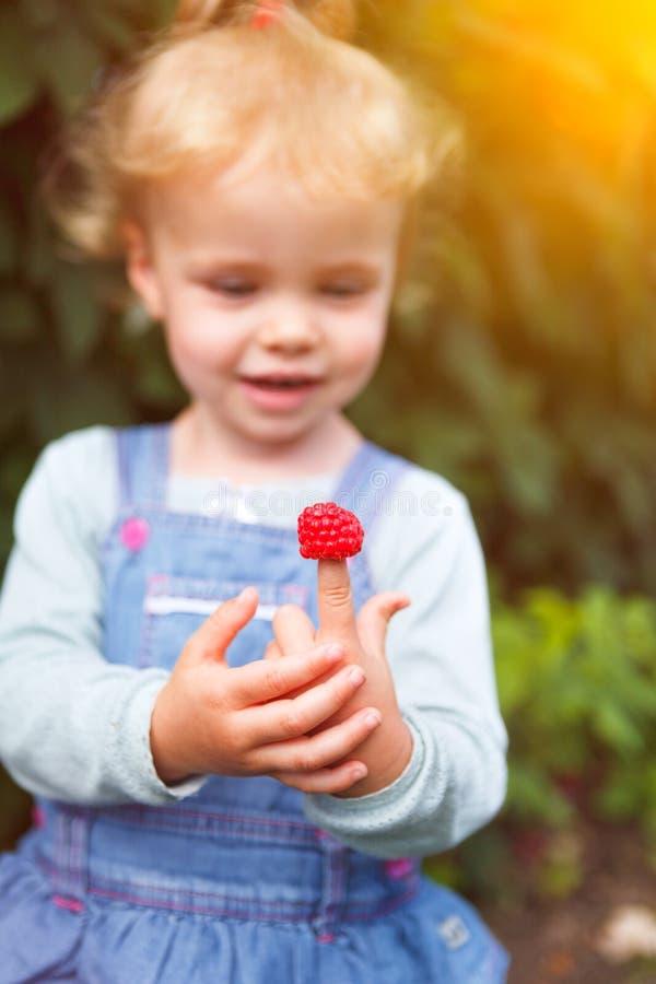 Liten flicka med hallonet på fingrar fotografering för bildbyråer