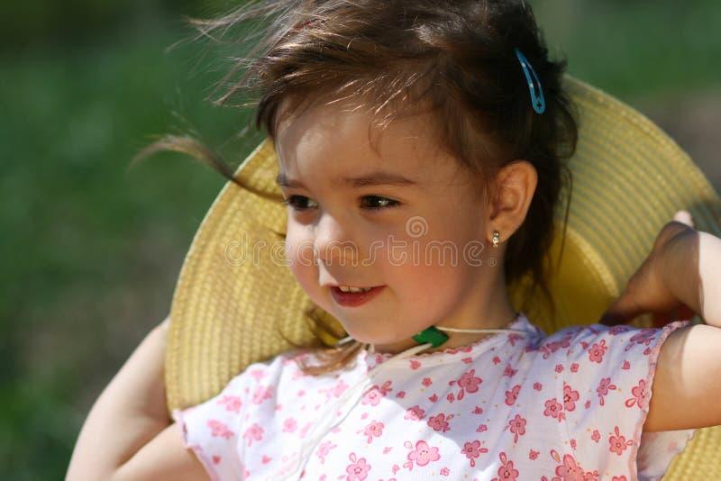 Liten flicka med hatten och hår i vind royaltyfria bilder