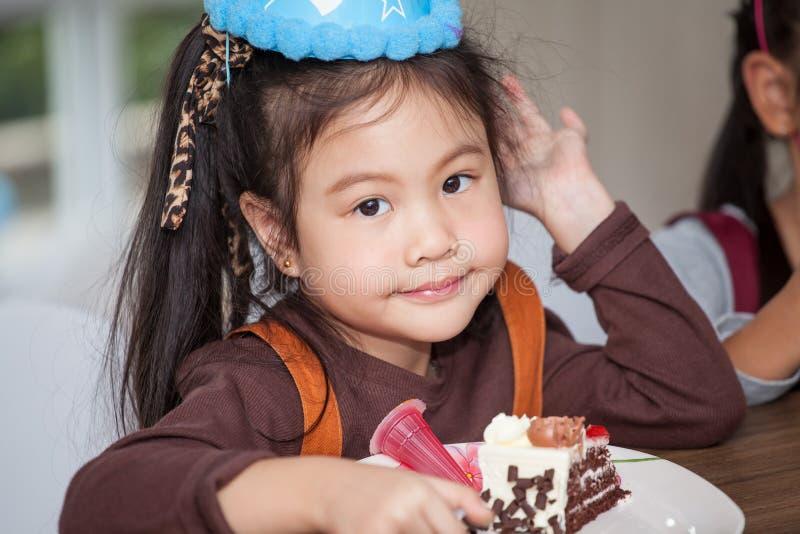 Liten flicka med hatten som äter födelsedagkakan royaltyfri fotografi