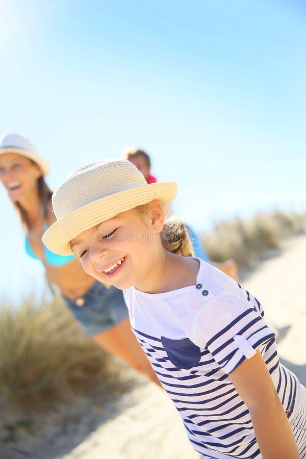 Liten flicka med hatten som kör till stranden med föräldrar royaltyfria bilder