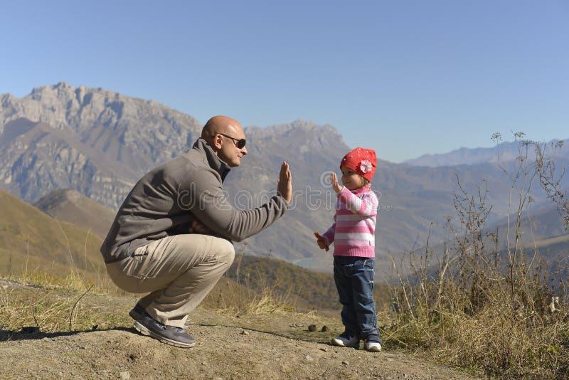 Liten flicka med hennes fader i bergen i höst royaltyfri foto