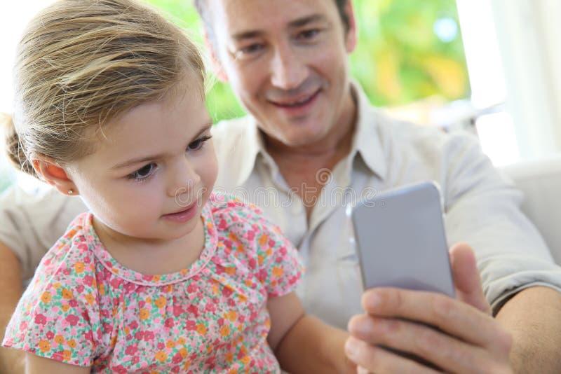 Liten flicka med hennes fader som använder en smartphone arkivfoto