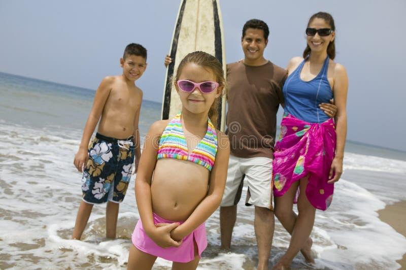 Liten flicka med hennes familj på stranden royaltyfri bild