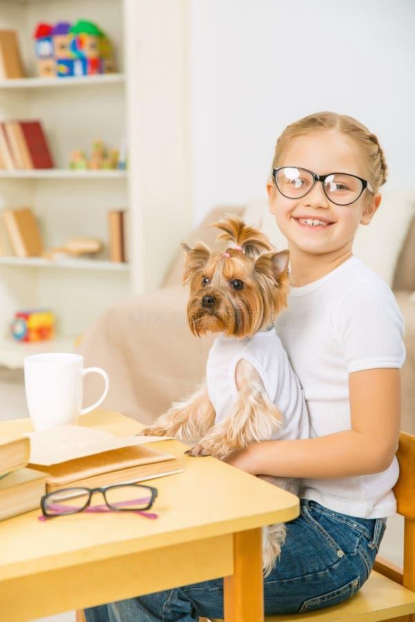 Liten flicka med hennes hund på skrivbordet arkivbild