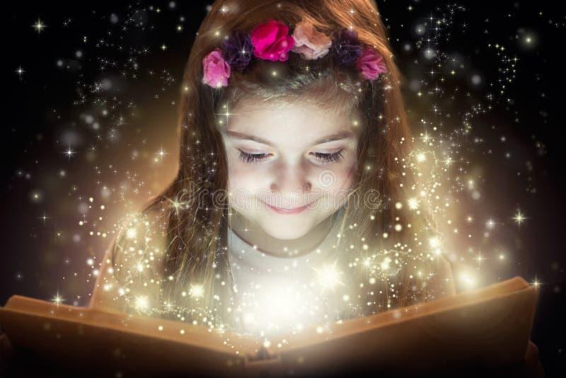 Liten flicka med hennes magiska bok royaltyfri bild