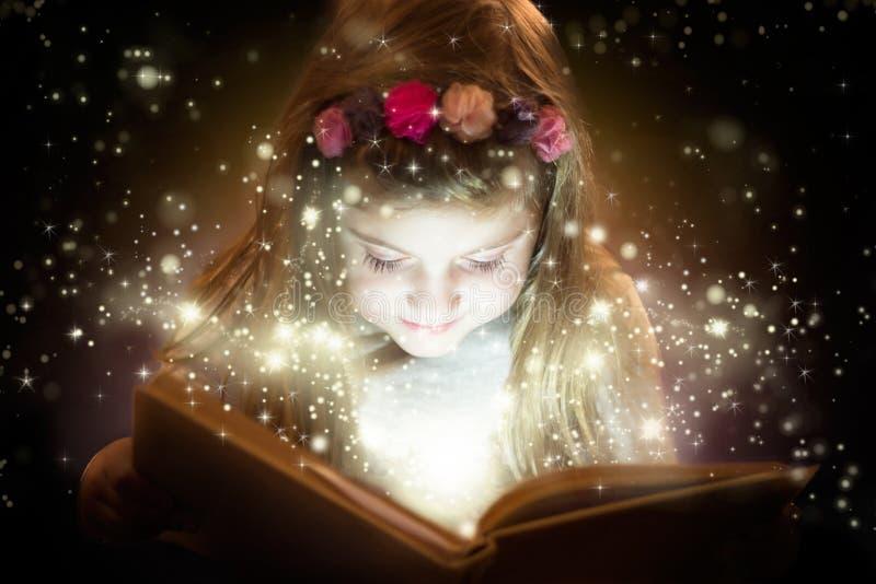 Liten flicka med hennes magiska bok royaltyfria bilder