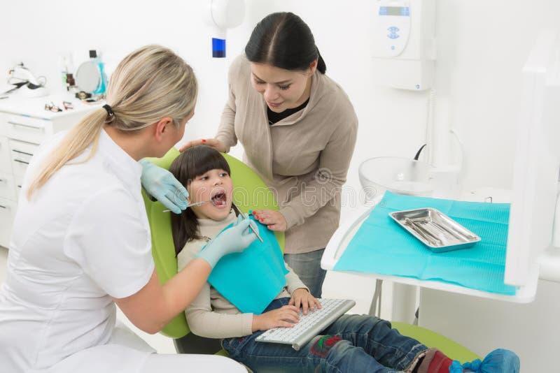 Liten flicka med hennes moder på tandläkares kontor arkivfoton