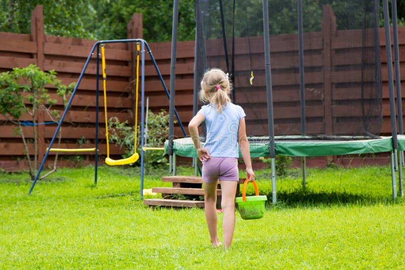 Liten flicka med hinken av vatten som går att tvätta hennes trampolin arkivfoton