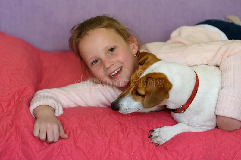 Liten flicka med hunden hemma i lekrum royaltyfri fotografi