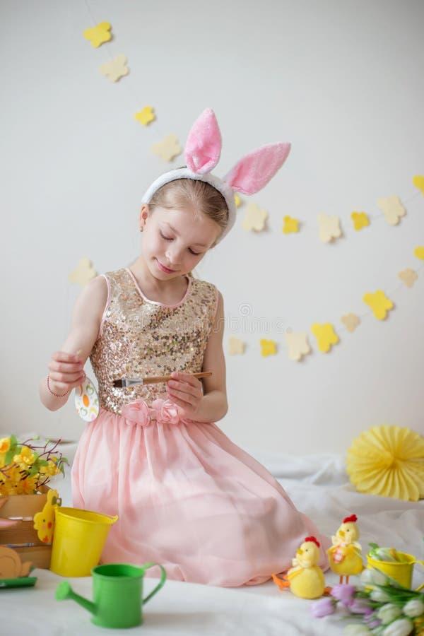Liten flicka med kaninöron som målar ägg, påskgarnering arkivfoton