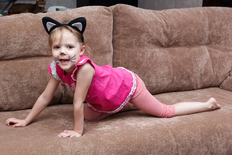 Liten flicka med kattframsidamålning på soffan royaltyfria bilder
