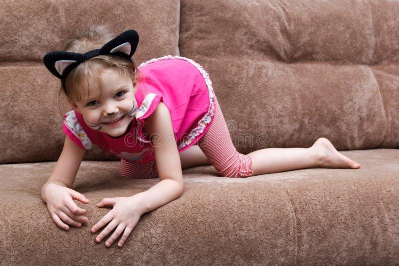 Liten flicka med kattframsidamålning på soffan royaltyfri fotografi