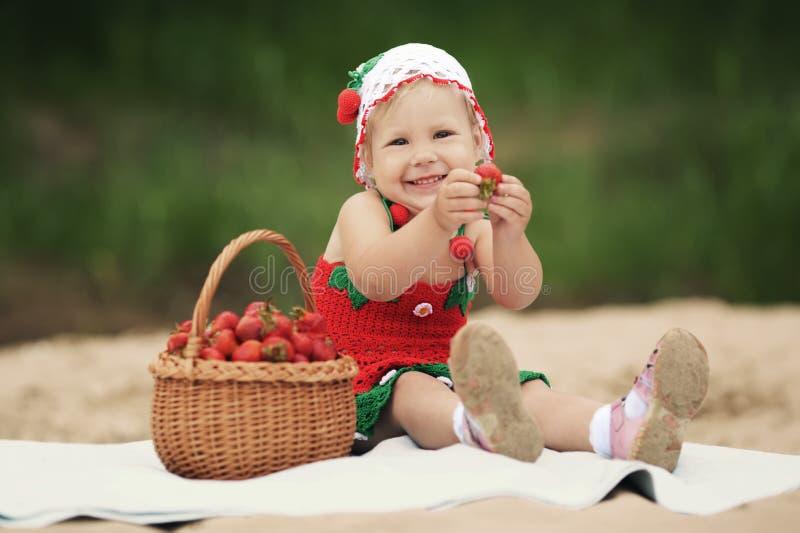 Liten flicka med korgen som är full av jordgubbar royaltyfri bild