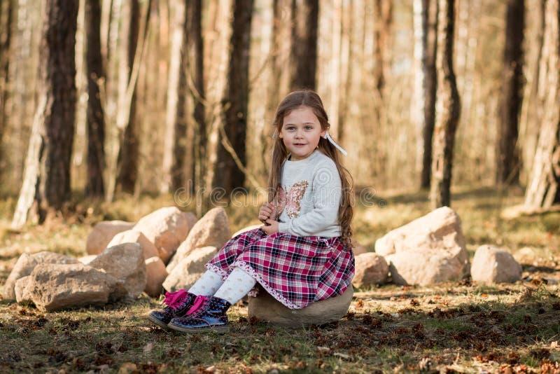 Liten flicka med långt hår som sitter i skogen arkivbilder