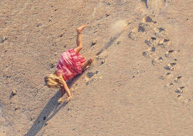Liten flicka med ljusa hårnedgångar från berget av sand arkivbilder