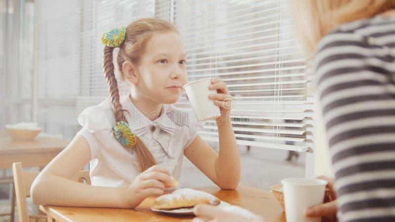 Liten flicka med mamman i det tonåriga kafét - förklarar något för moder arkivbilder