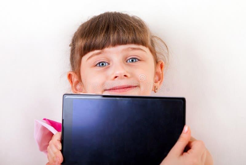 Liten flicka med minnestavladatoren royaltyfri fotografi