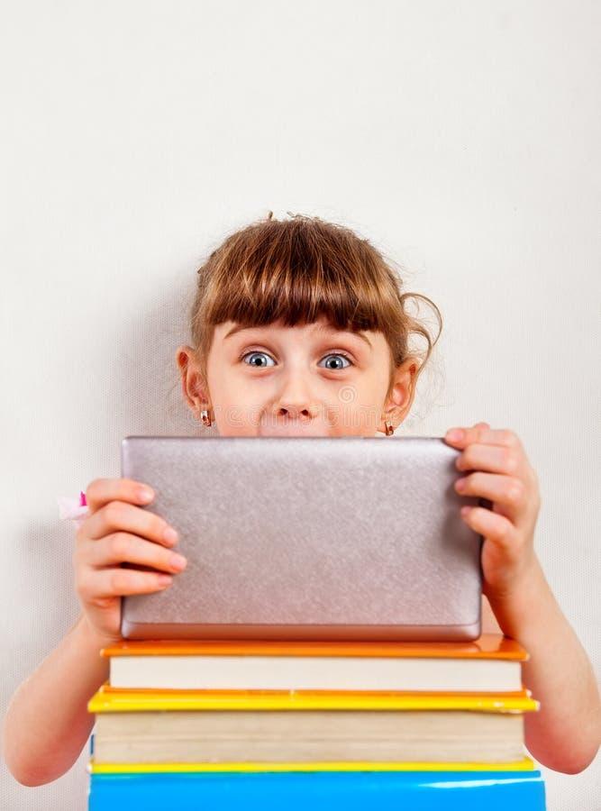 Liten flicka med minnestavladatoren royaltyfri bild
