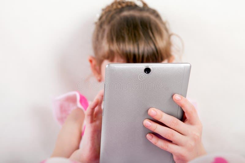 Liten flicka med minnestavladatoren arkivfoto
