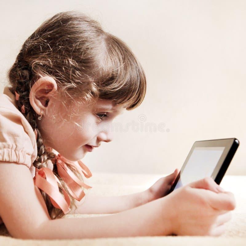 Liten flicka med minnestavladatoren royaltyfria bilder