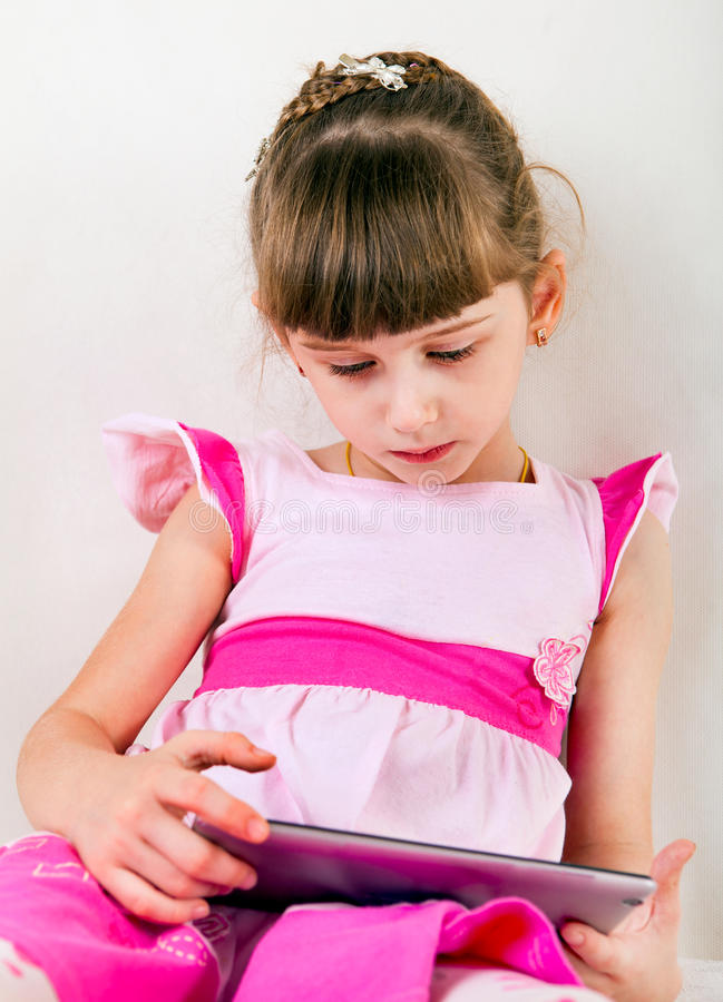 Liten flicka med minnestavladatoren arkivfoton