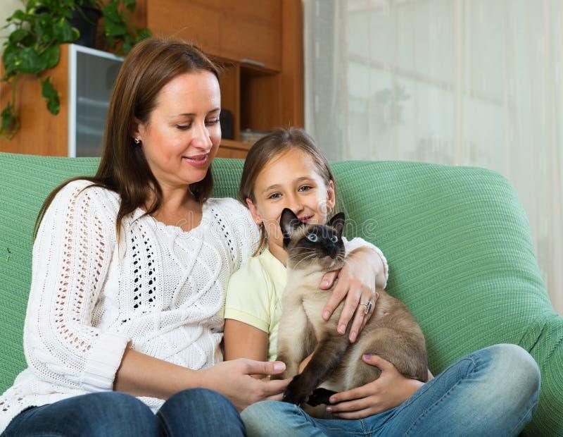 Liten flicka med modern och den Siamese katten fotografering för bildbyråer