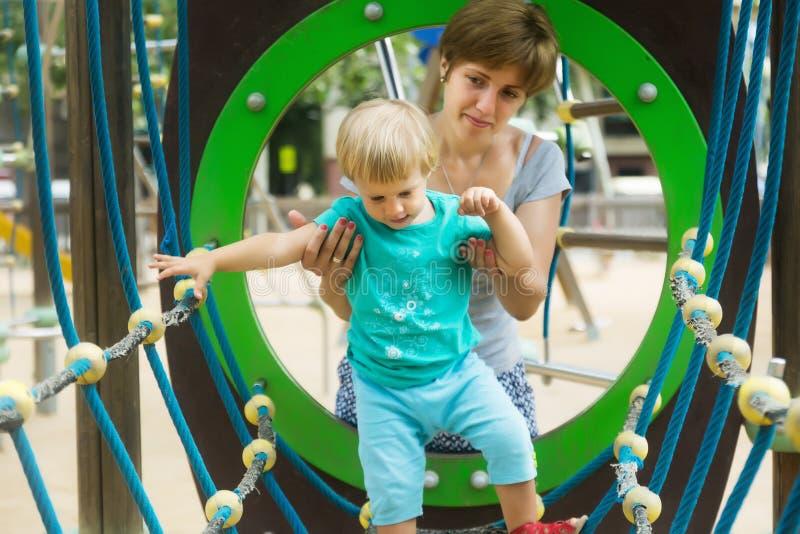 Liten flicka med modern på denorienterade lekplatsen arkivfoto
