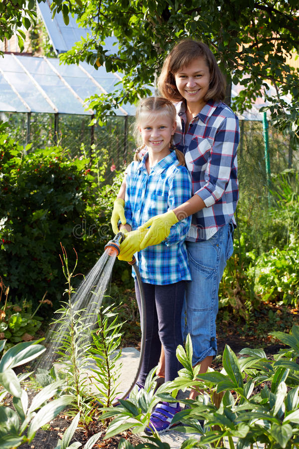 Liten flicka med modern som bevattnar blommor på gräsmattan royaltyfri bild
