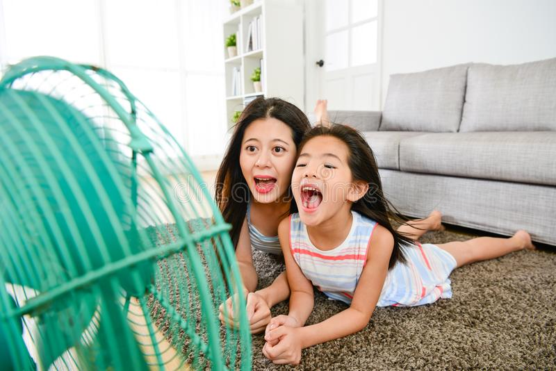 Liten flicka med modern som spelar den elektriska fanen royaltyfria foton
