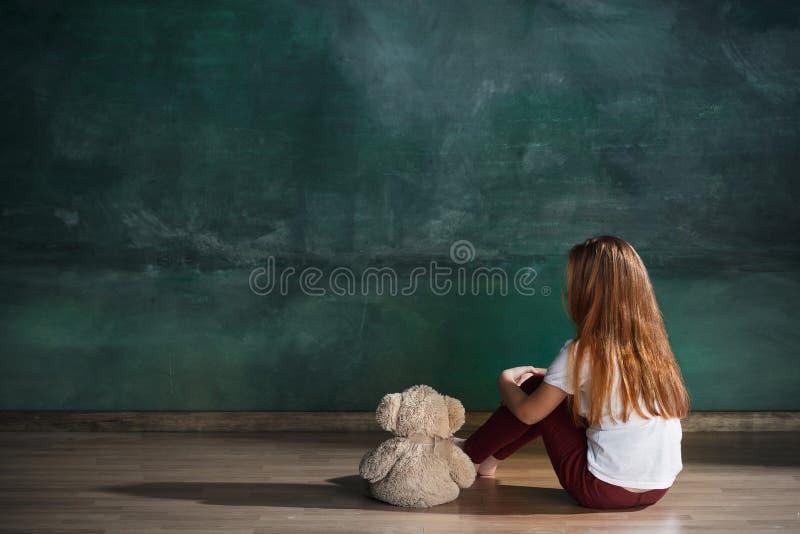 Liten flicka med nallebjörnen som sitter på golv i tomt rum Autismbegrepp arkivbilder