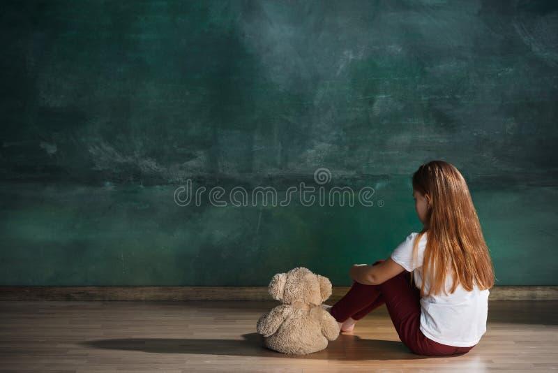 Liten flicka med nallebjörnen som sitter på golv i tomt rum Autismbegrepp arkivbild