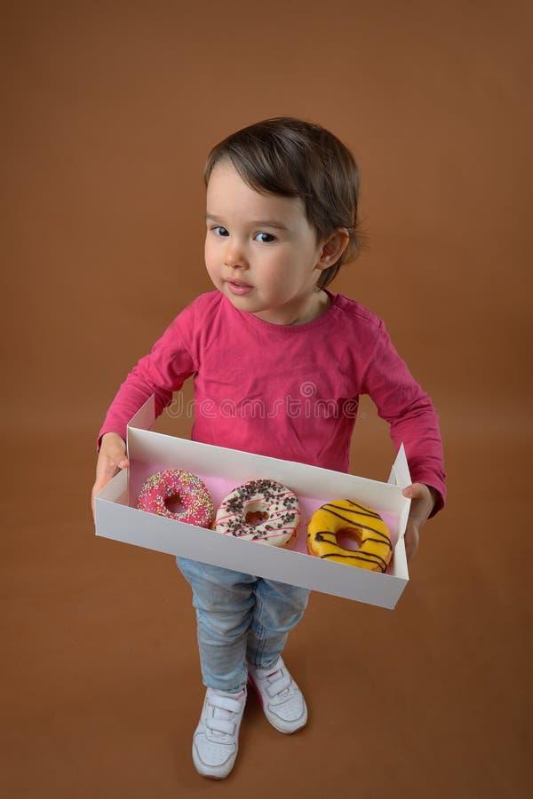 Liten flicka med olika donuts royaltyfria foton